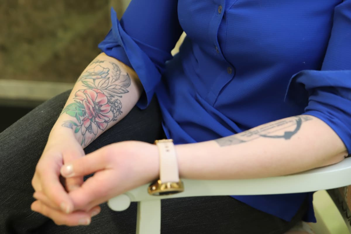 Minttu Väisäsen kädet, hihat käärittyinä ja tatuoinnit näkyvillä.
