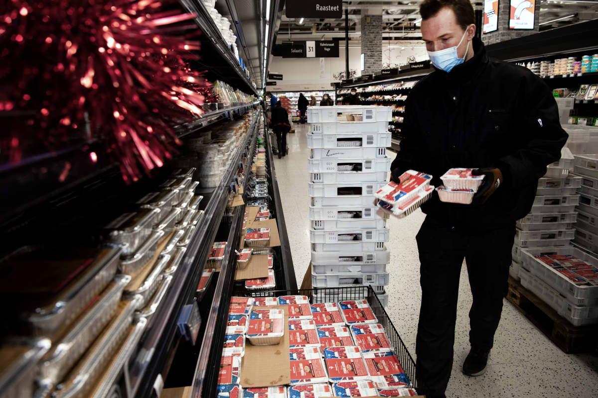 Niklas Skutnabb täyttää ruokakaupan hyllyjä joululaatikoilla.