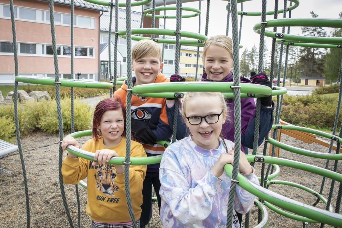 Hymyileviä lapsia kiipeilytelineessä koulun pihalla.
