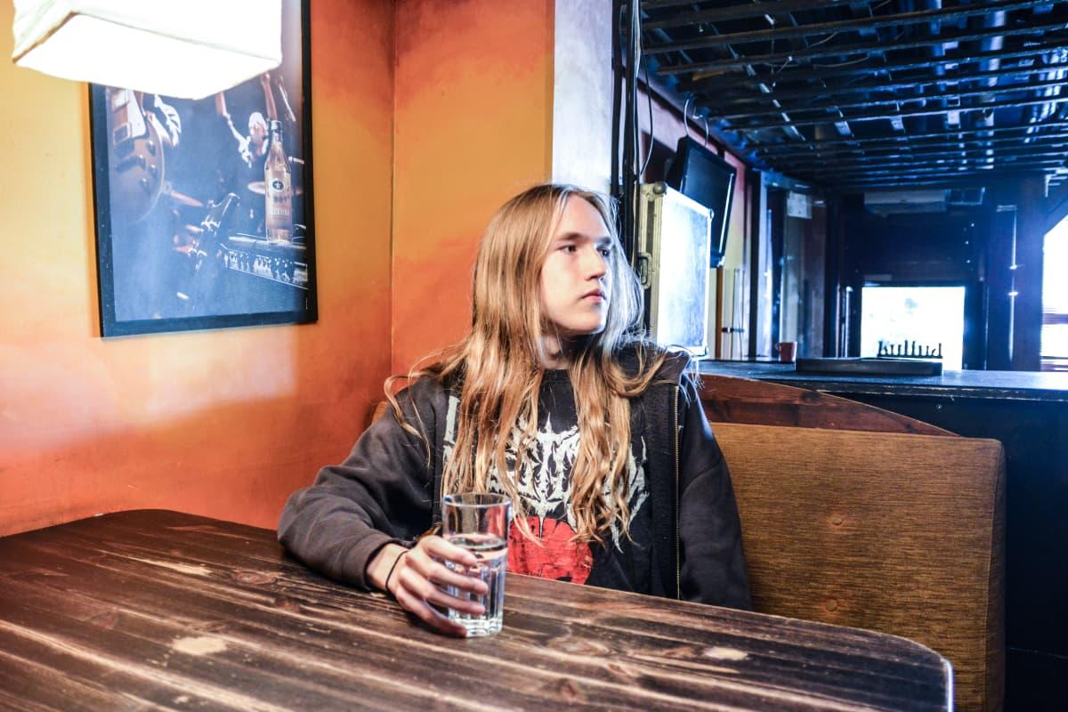 Juuso Parviainen istuu Kajaanin Rock House Kulman pöydässä ja katsoo oikealle.