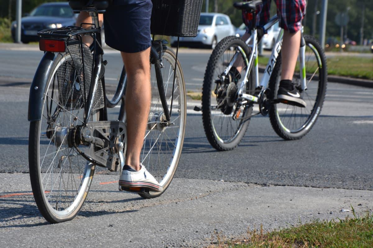 Kaksi polkupyöräilijää tiellä.