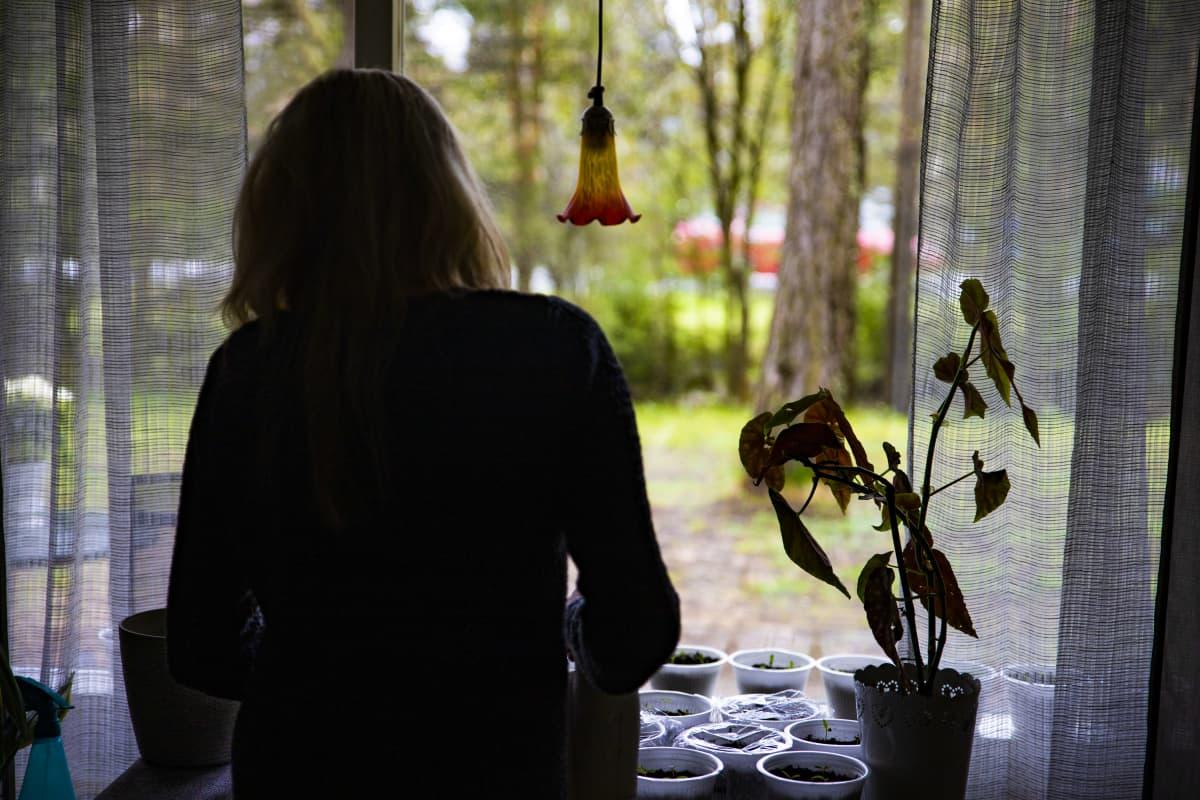 Erityislapsen äiti kastelee kukkia.