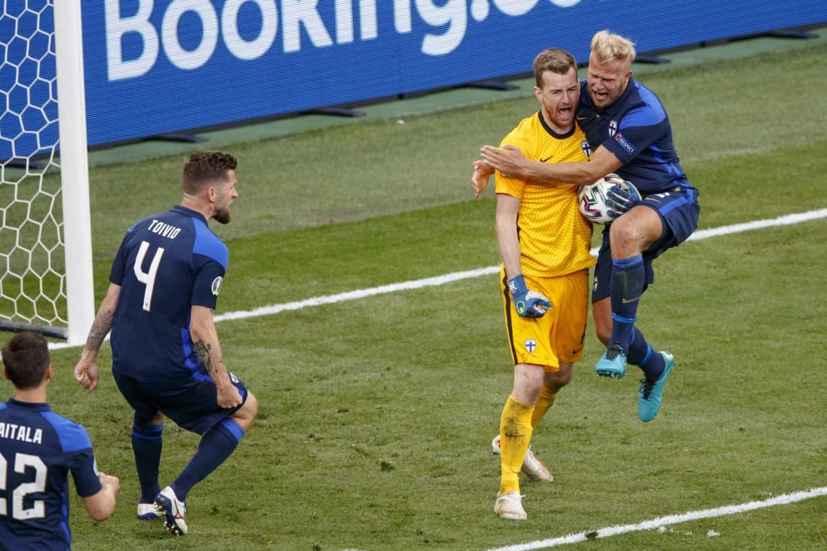 Lukas Hradecky torjuu rankkarin Tanskaa vastaan, ja Paulus Arajuuri hyppää syliin.