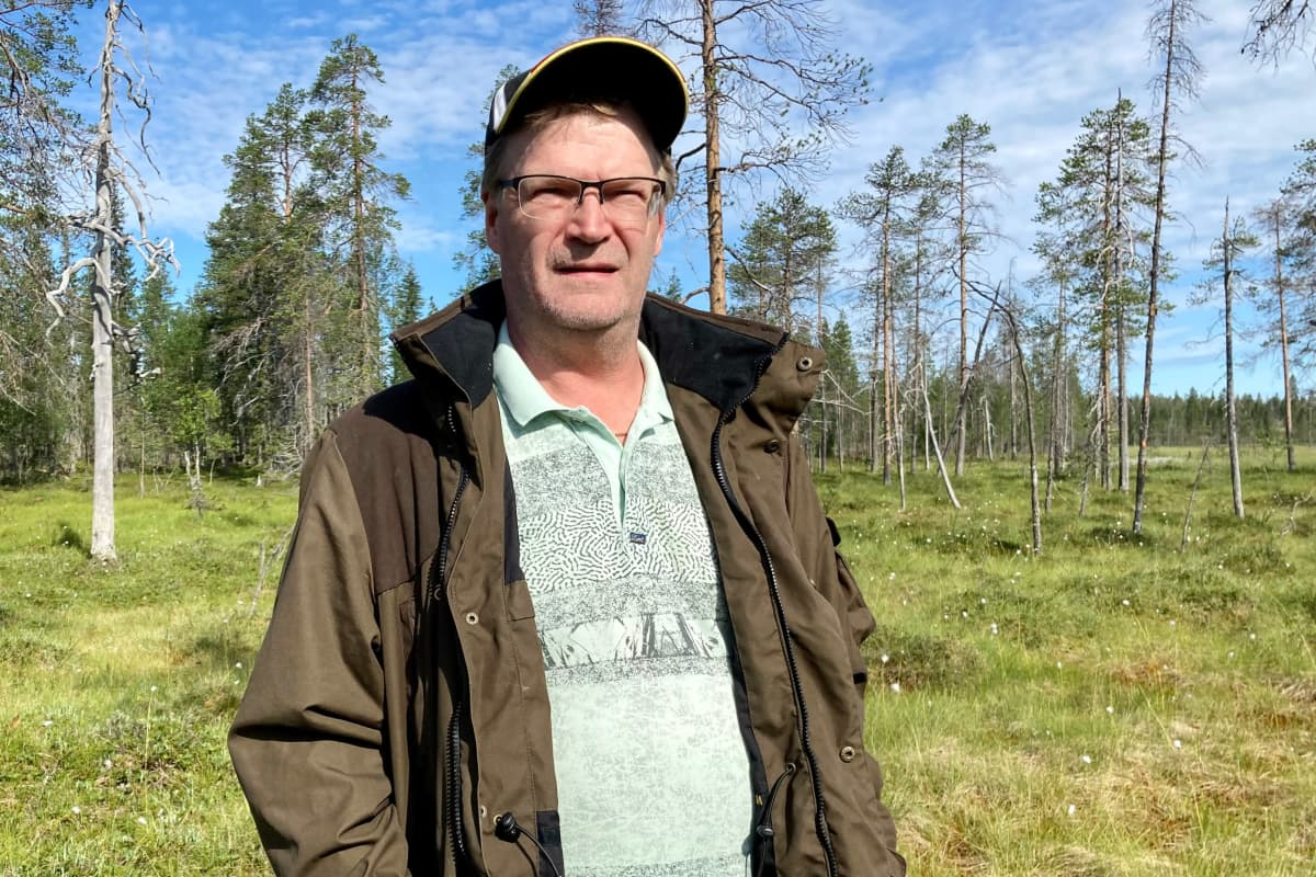 Vihreään eräasuun pukeutunut Lapin tuorelakka Oy:n toimitusjohtaja Jari Huttunen hillasuo taustanaan.