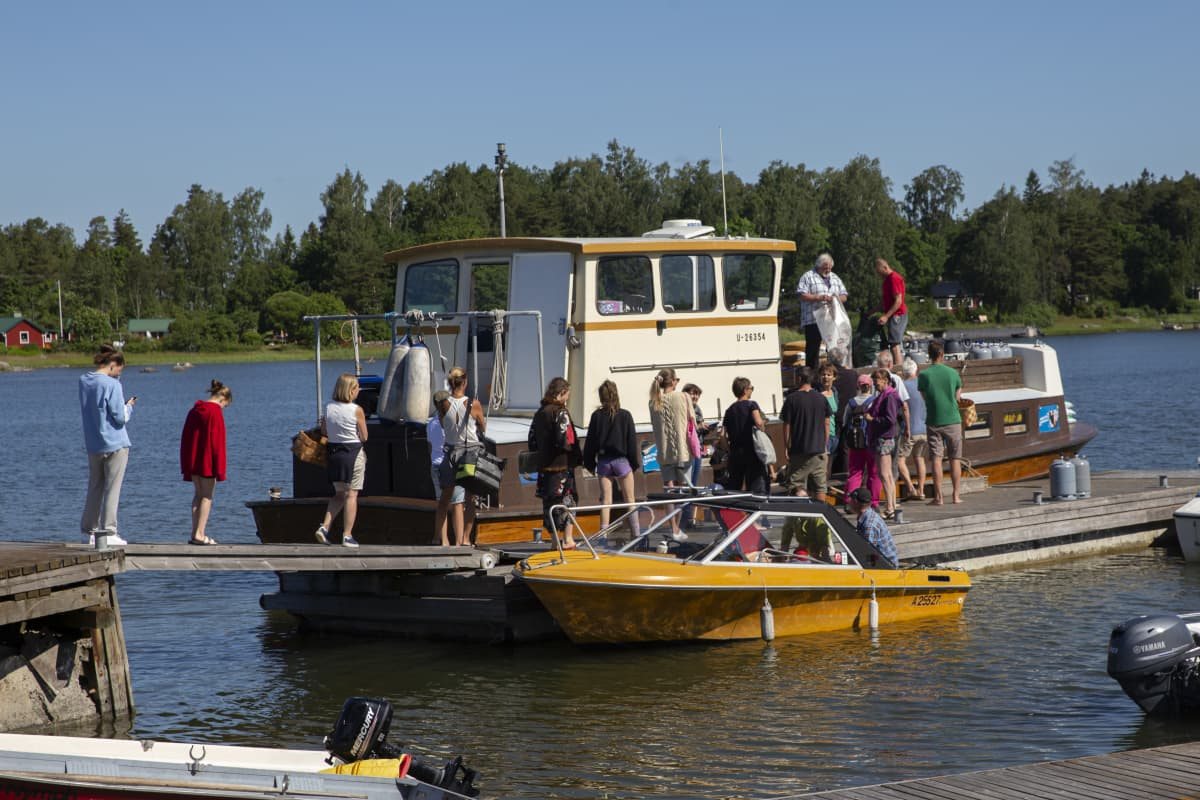 Ihmiset jonottavat kauppalaiva Christinaan Pirttisaaren laivalaiturilla.
