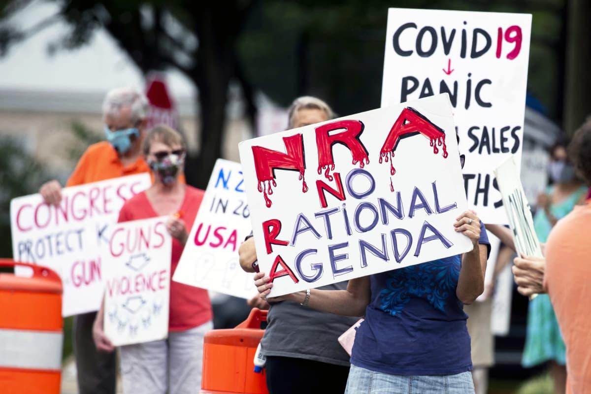 Mielenosoittajat pitelevät NRA:ta ja aseita vastustavia kylttejä.