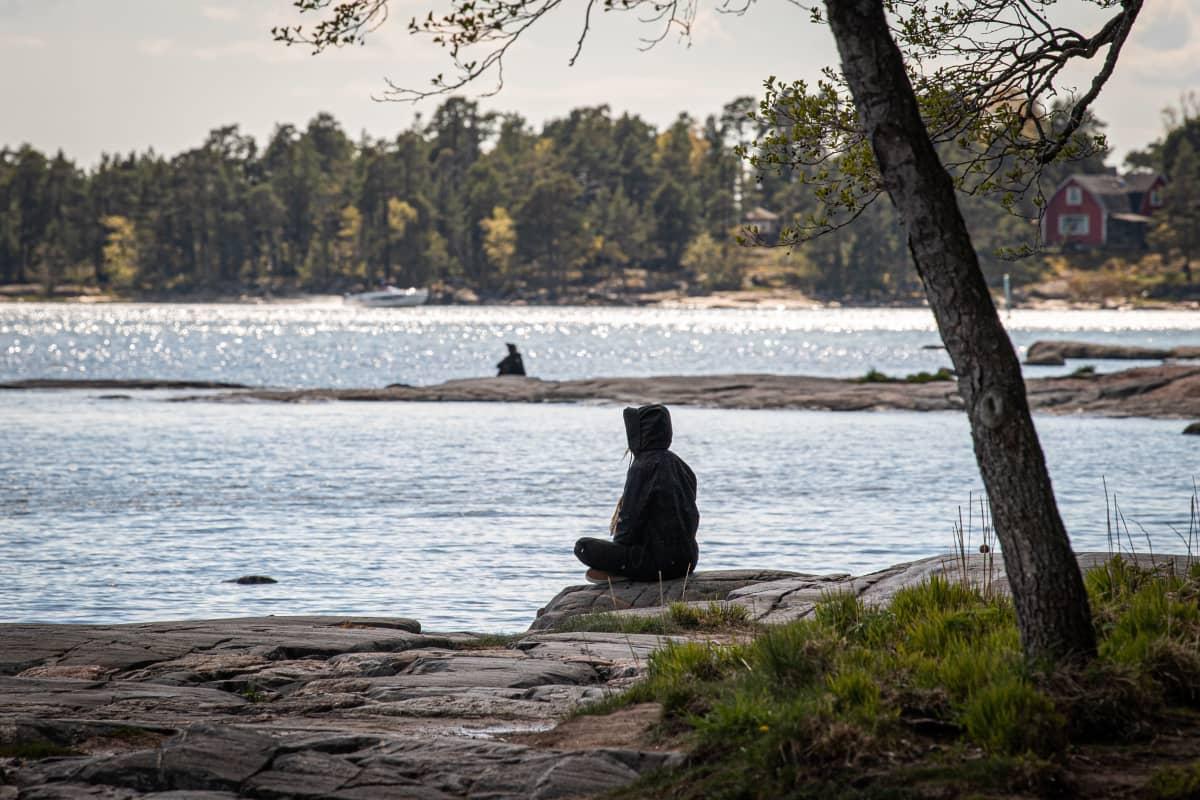 Ihminen istuu risti-istunnassa meren rannalla katsoen ulapalle.