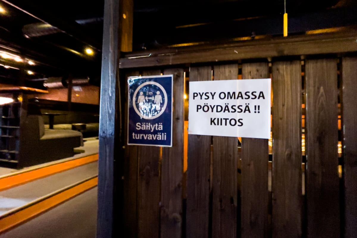 """Bar Q -ravintolassa Imatralla koronarajoitus -kylttejä sisällä. """"Säilytä turvaväli"""" ja """"Pysy omassa pöydässä!! Kiitos""""."""