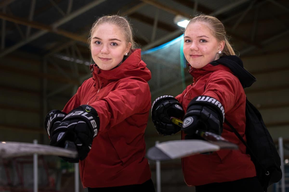 Iida (vas.) ja Emma Lappalainen punaisissa takeissa, jääkiekkohanskat kädessä, ojentamassa jääkiekkomailoja kameraa kohti.