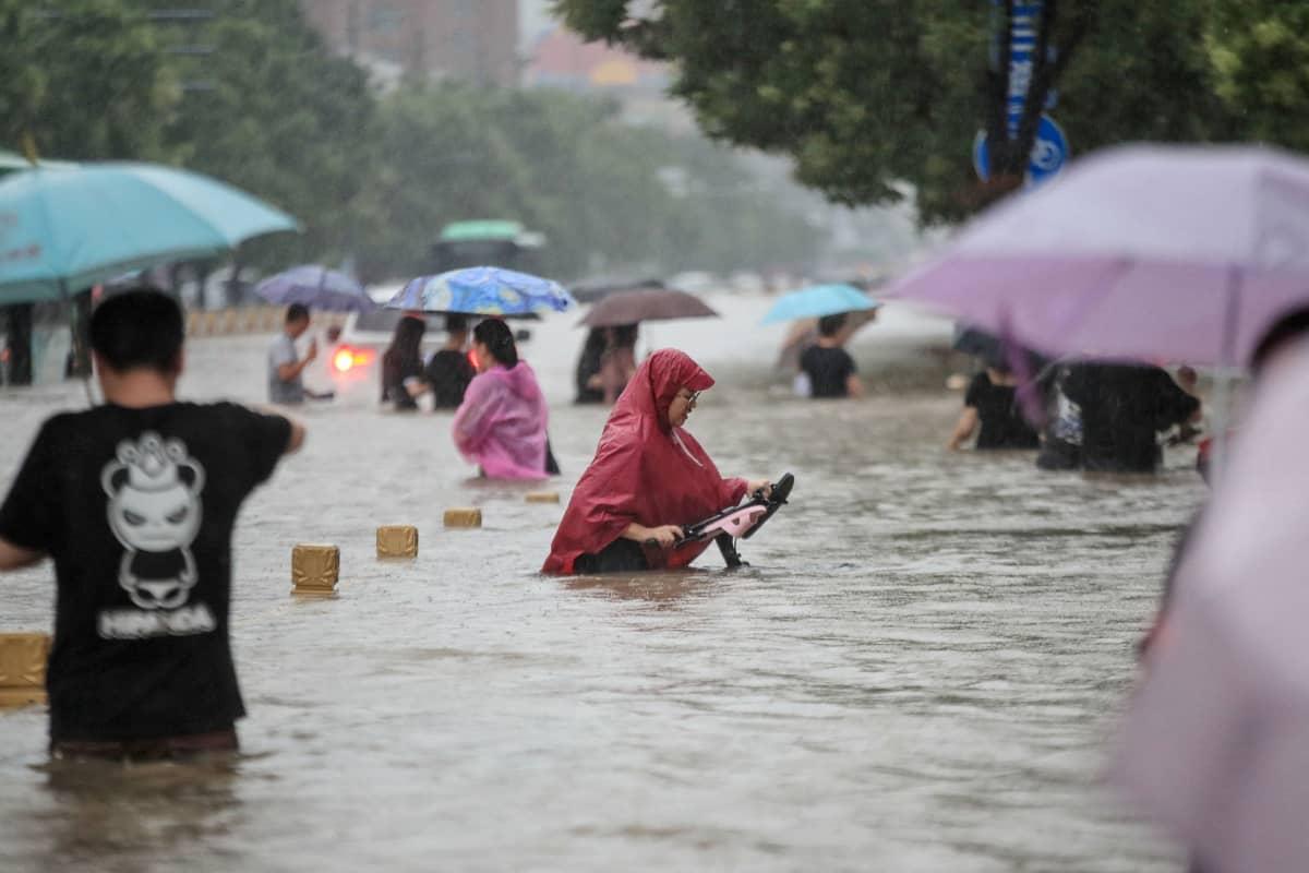 Ihmiset kävelevät tulvivalla kadulla sateenvarjojen ja sadeasujen kanssa.