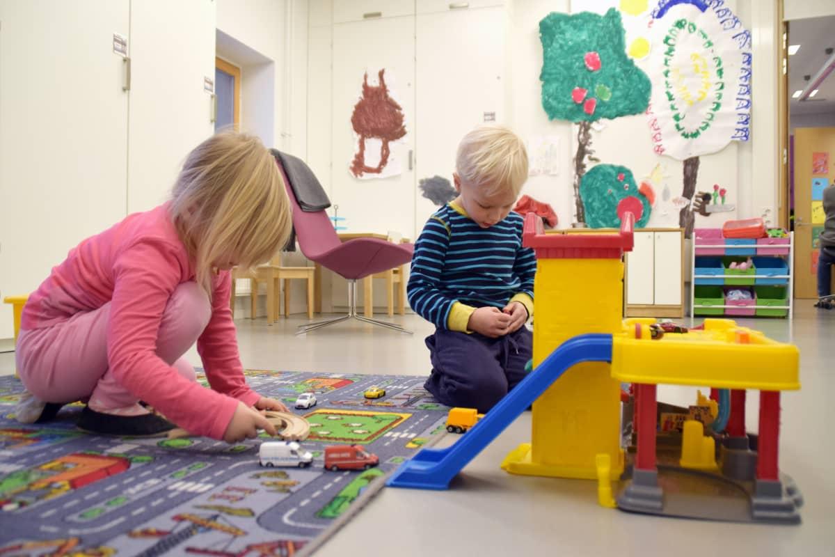 Två barn leker med bilar vid en bilbana.