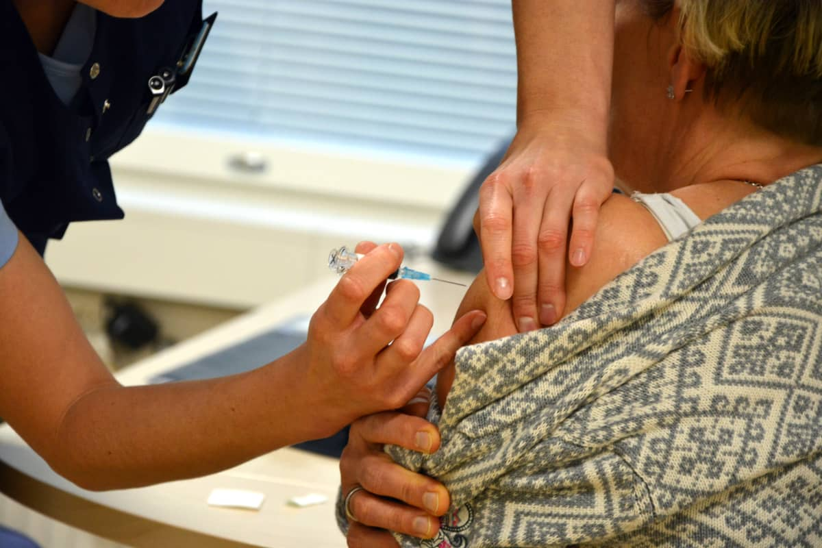 Terveydenhoitaja rokottaa naista käsivarteen.
