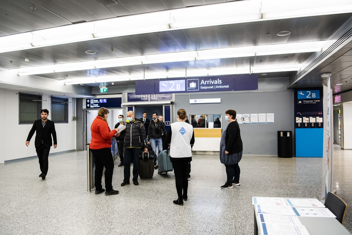 Kuvassa kausityöläisiä ohjeistetaan lentoasemalla karanteenisäännöistä.