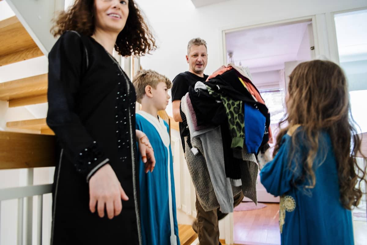 Kuvassa perheen isä Mathias kantaa pyykkejä, Nadia ja lapset seuraavat vierestä.