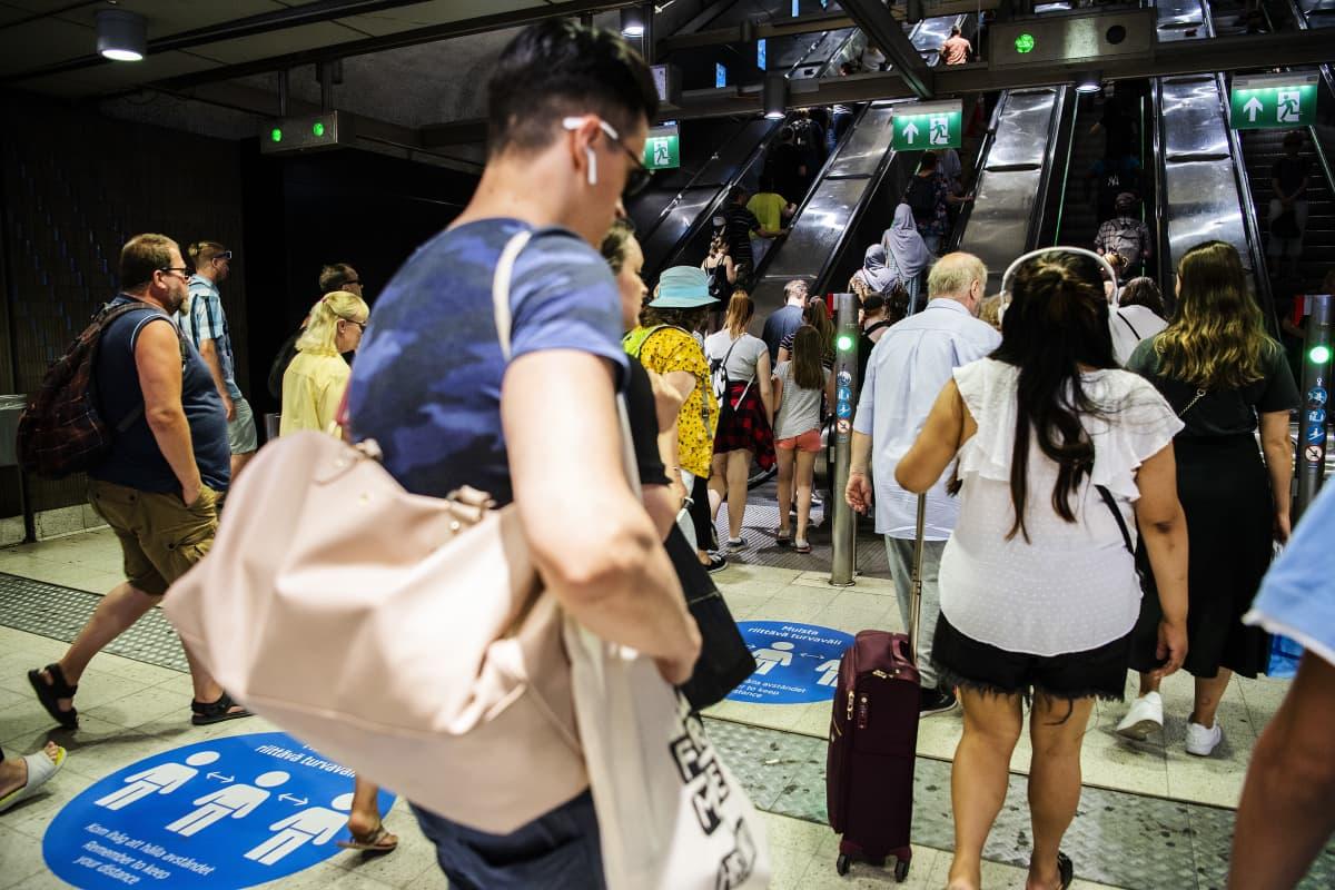 Ihmiset poistuivat metroasemalta Helsingissä kesäkuun lopulla 2020.