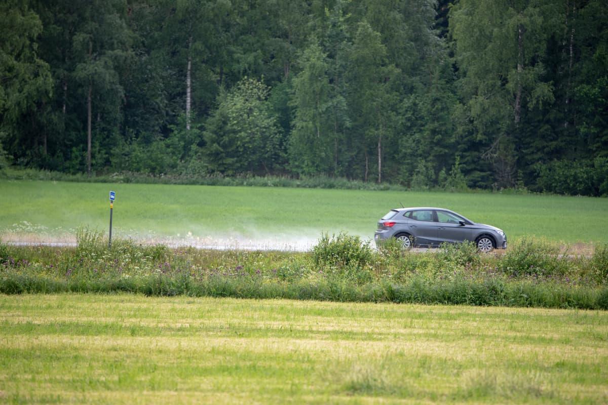 Henkilöauto ajaa sateisella tiellä peltojen keskellä.