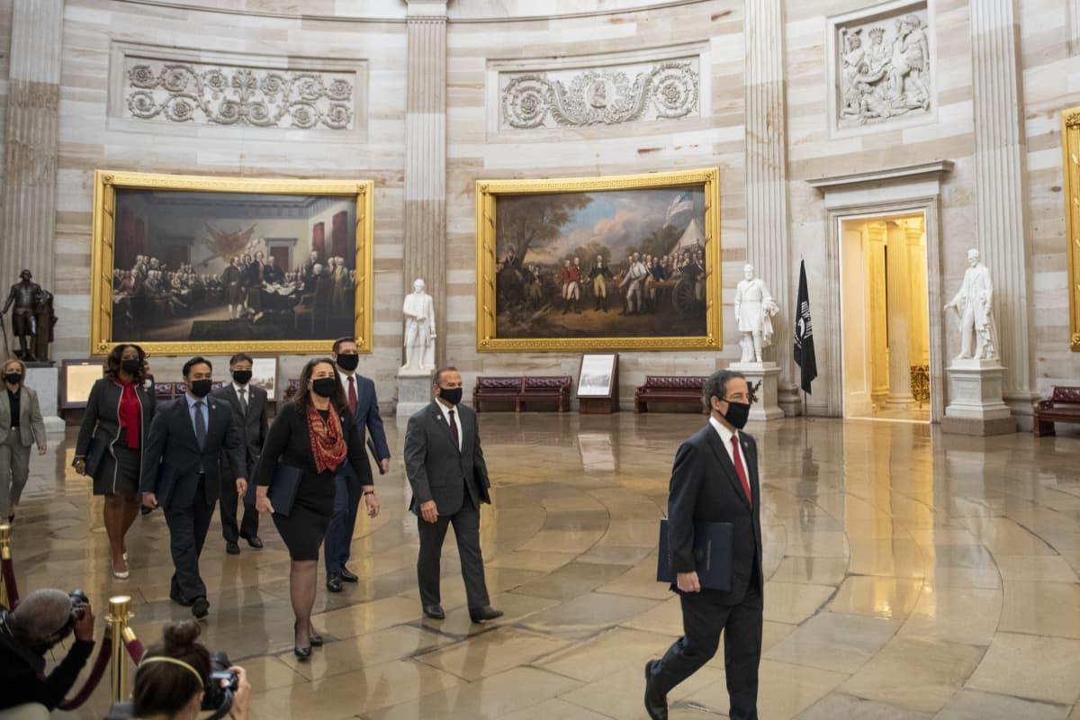 Kongressiedustajat kävelevät koristeellisen salin halki maskit kasvoillaan