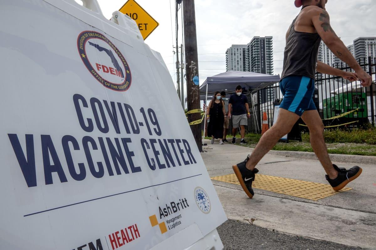 Koronarokotuspaikan kyltti ja sen ohitse kulkeva shortseihin pukeutunut ihminen Floridassa