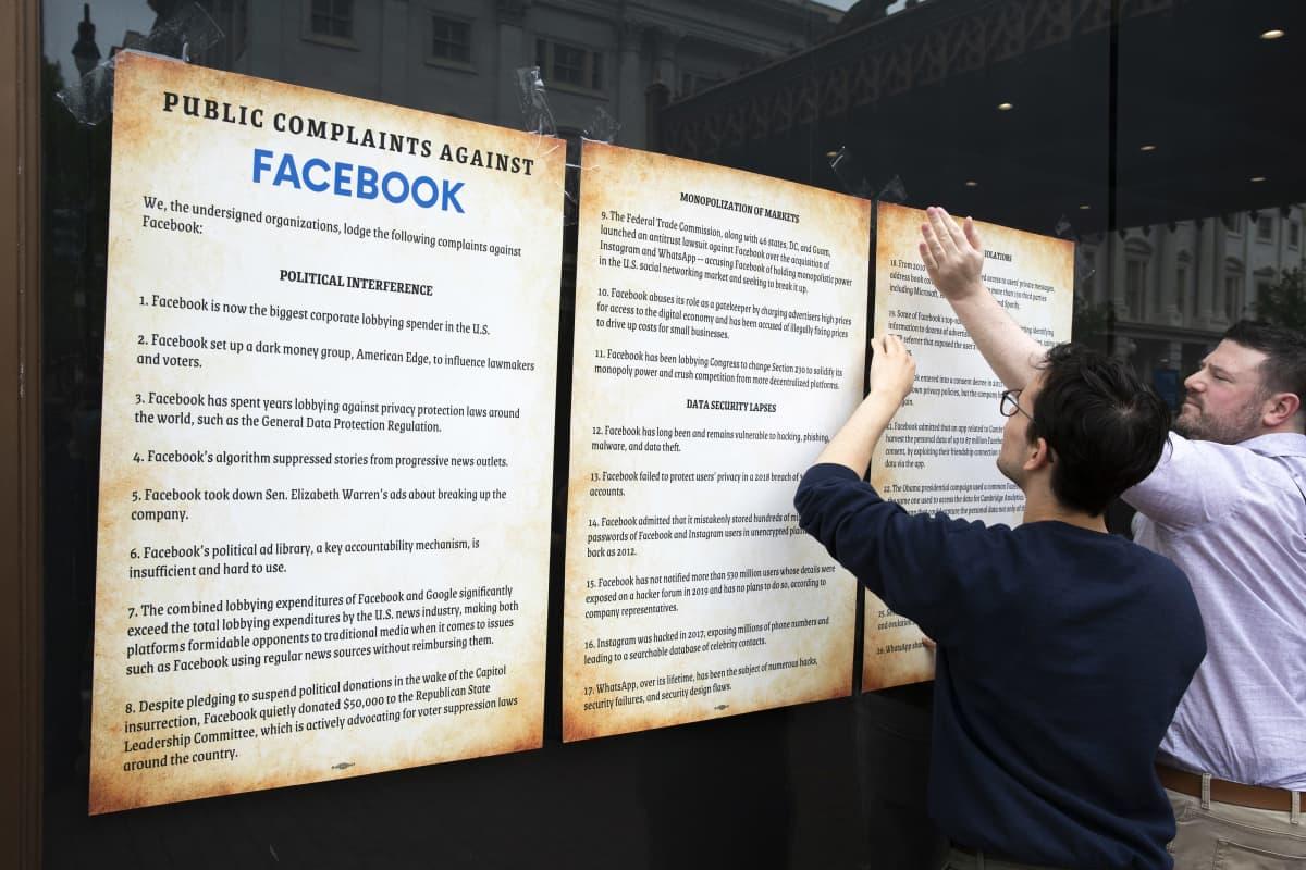 Aktivistit laittavat ikkunaan kiinni julisteita joissa kerrotaan valituksista Facebookkia vastaan.