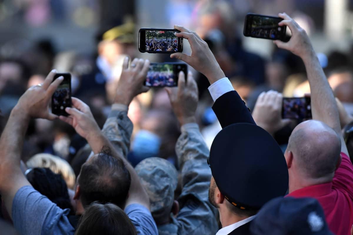 Muistotilaisuuten osallistuvat kuvaavat puhelimillaan tilaisuutta.