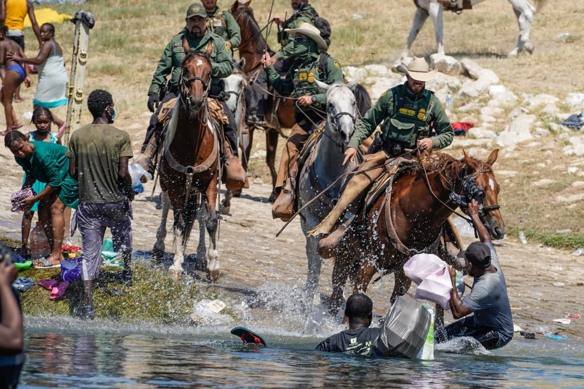 USA:n rajavartioston työntekijä astuu hevosen selässä uhkaavasti kohti siellä käveleviä, siirtolaisia. Hänellä on ruoska kädessään, ja hän käyttää sitä edessään joessa olevaan ihmiseen.