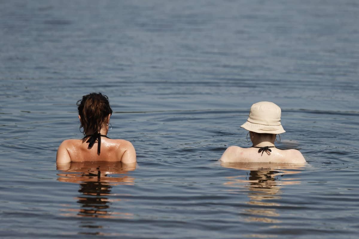 Kaksi ihmistä selin kameraan vedessä.