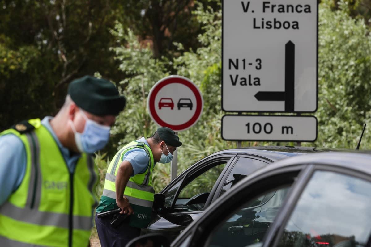 Maskipäiset poliisit valvomassa Lissabonista poistuvaa liikennettä koronarajoitusten vuoksi.