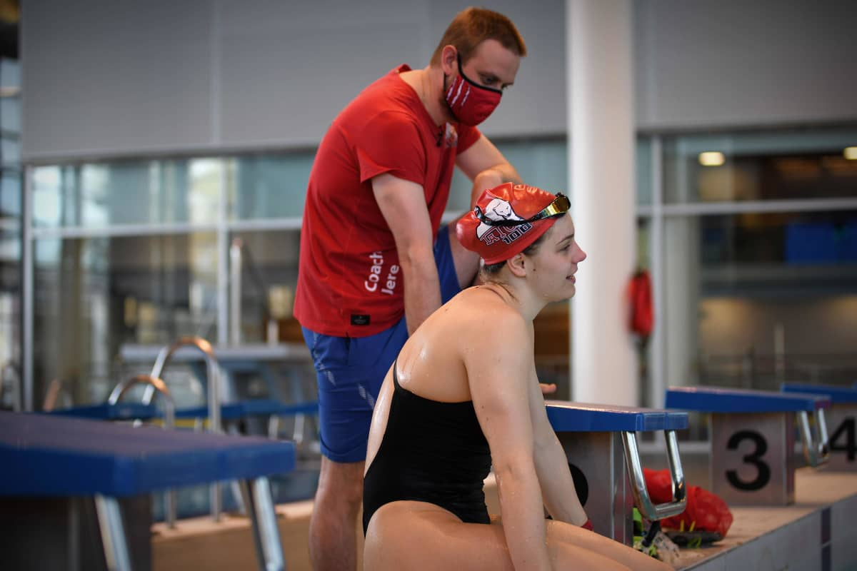 Ida Hulkko pratar under simträningar i Tammerfors. I bakgrunden tränaren Jere Jännes.