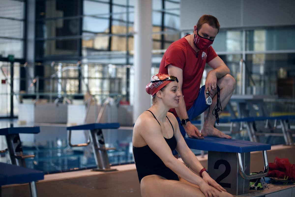 Ida Hulkko ler under simträningar i Tammerfors. I bakgrunden tränaren Jere Jännes.