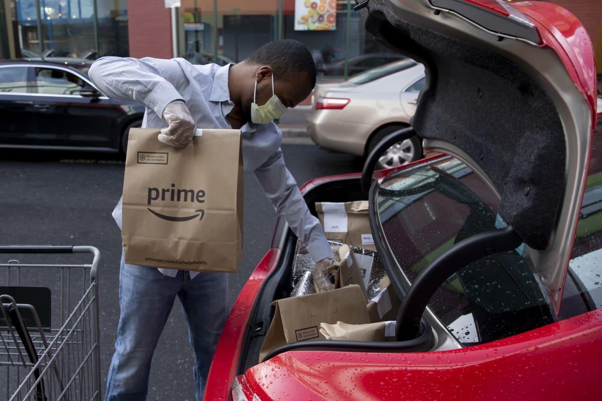 Amazonin kuljettaja lastaa ruokatoimituksia autoon Silver Springsissä, Marylandissä, 7.4.2020.