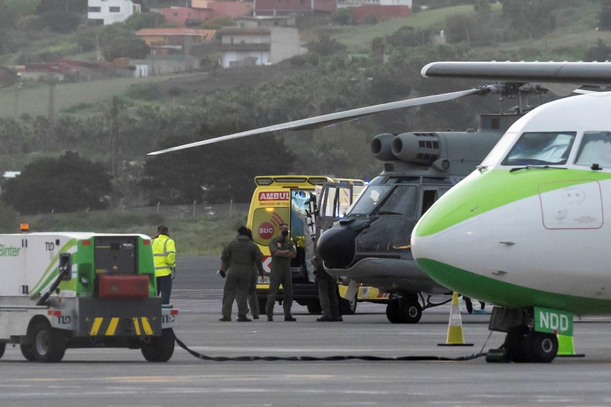 Ambulanssi, helikopteri ja lentokone lentokentällä.