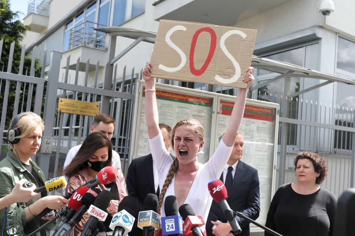 Aktivisti Jana Shostak pitää päänsä yläpuolella kylttiä, jossa lukee SOS ja huutaa. Meneillään on tiedotustilaisuus Valko-Venäjän lähetystön edessä.