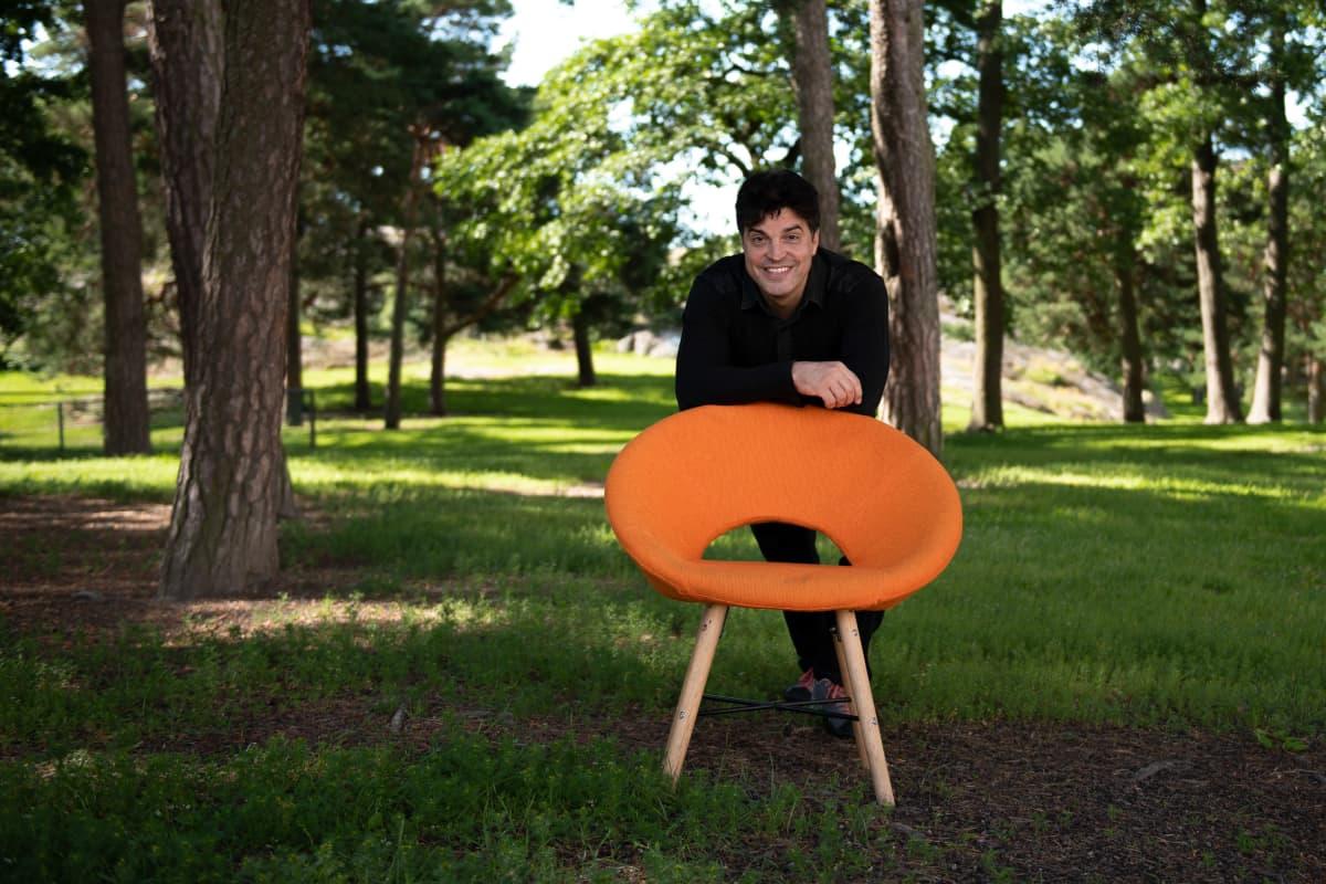 Mies nojaa oranssiin tuoliin puistossa.