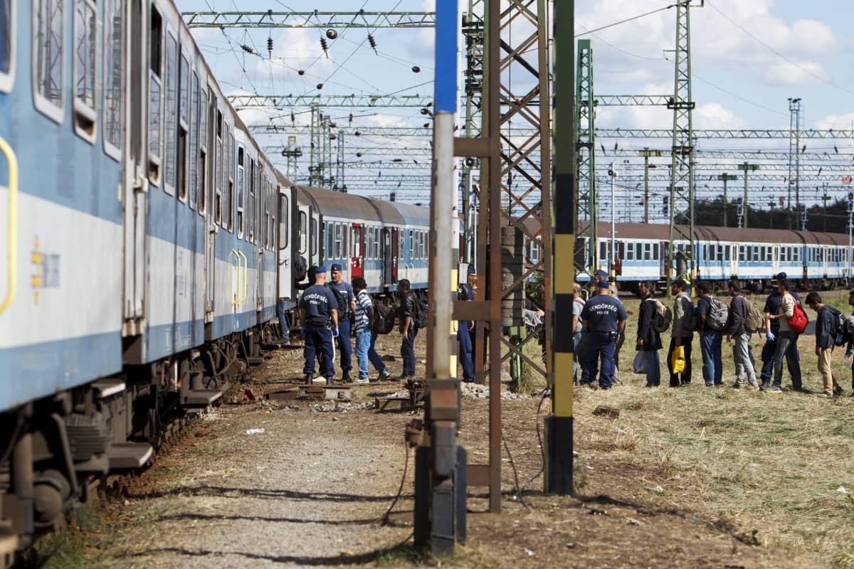 Poliisi ohjaa turvapaikanhakijoita junaan.