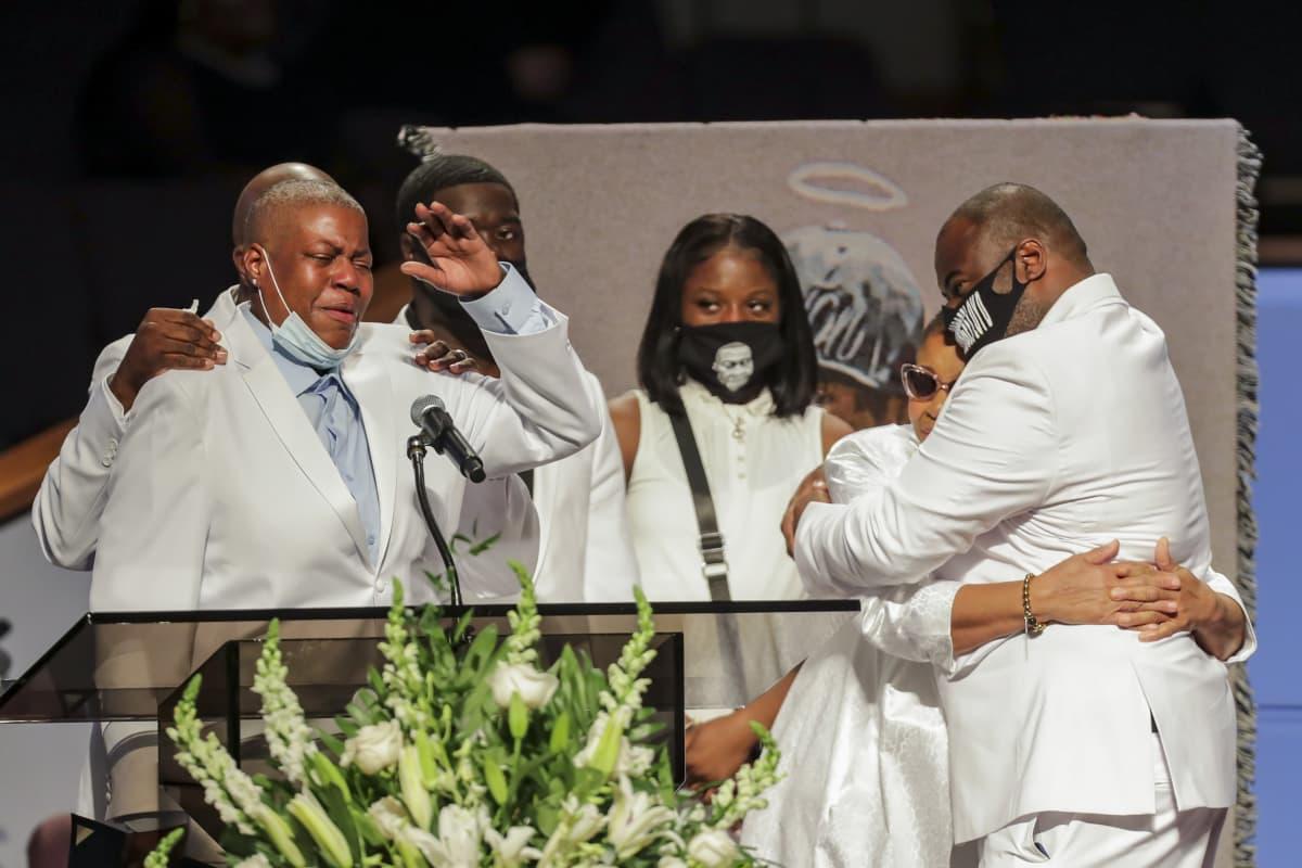 LaToya Floyd puhuu ympärillään valkoisiin pukeutuneita sukulaisia.