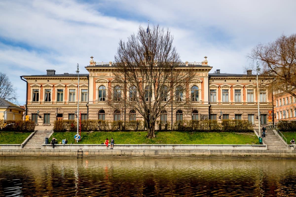 Muutamia ihmisiä istuu aurajoen rannalla Turun kaupungintalon edessä.