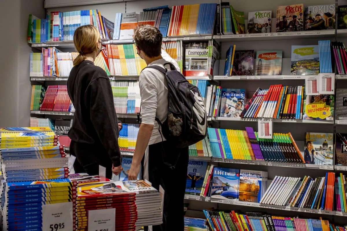 Asiakkaita tutkimassa oppikirjoja Suomalaisessa Kirjakaupassa Helsingissä