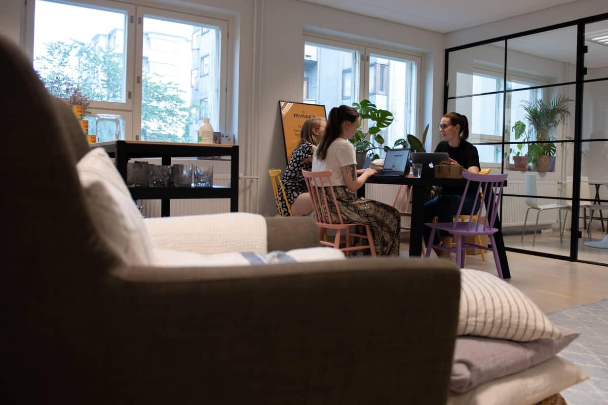 Outi Ellilä, Annika Ikonen ja Hetta Ahokas pitävät kokousta pöydän ääressä ikkunan edessä. Etualla näkyy nojatuoli.