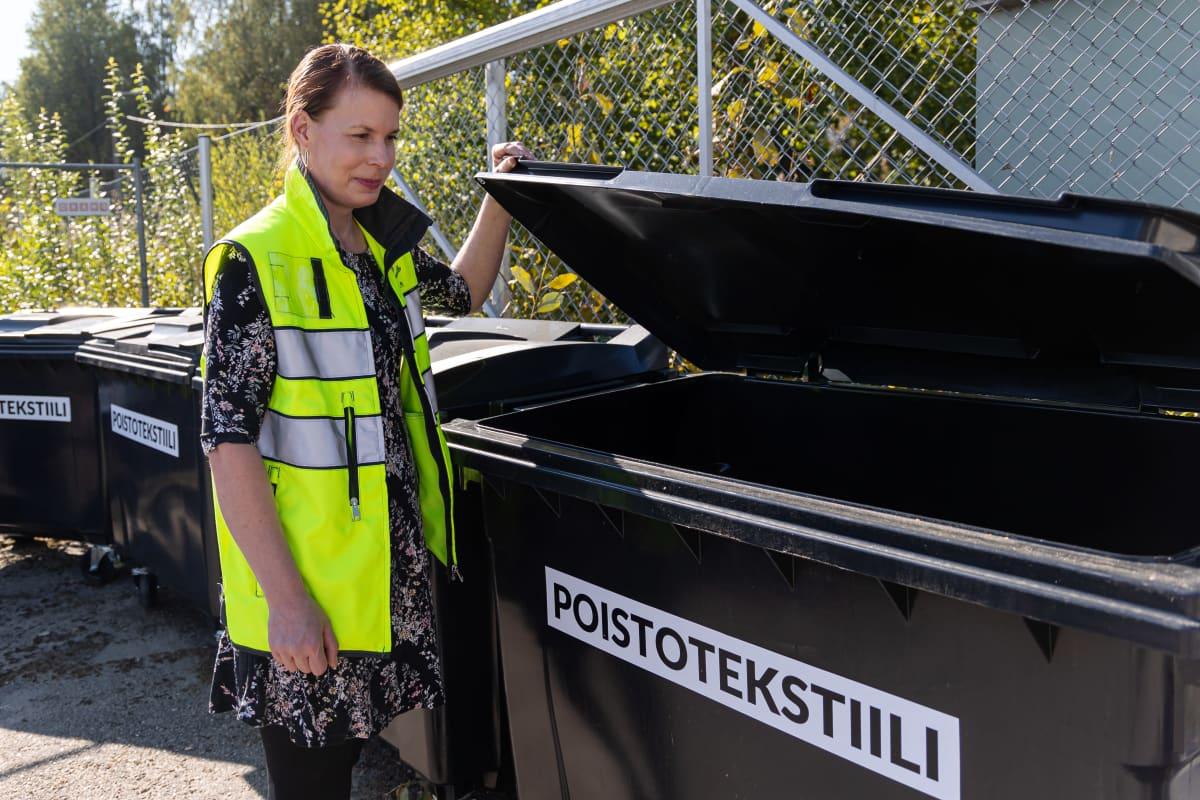 Etelä-Karjalan jätehuollon asiakaspalvelupäällikkö Mari Ilvonen raottaa poistotekstiili jäteastian kantta Imatralla.