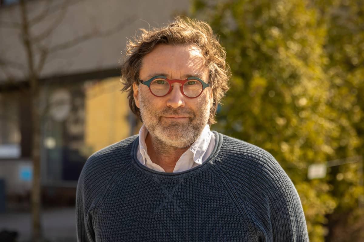 Erik Söderblom ulkona. Erikillä on silmälasit, sininen tumma villapaita ja alla valkoinen kauluspaita. Parransänkeä on muutama millimetri. Taustan puussa ei ole vielä lehtiä, mutta kuuset ovat vihreitä.