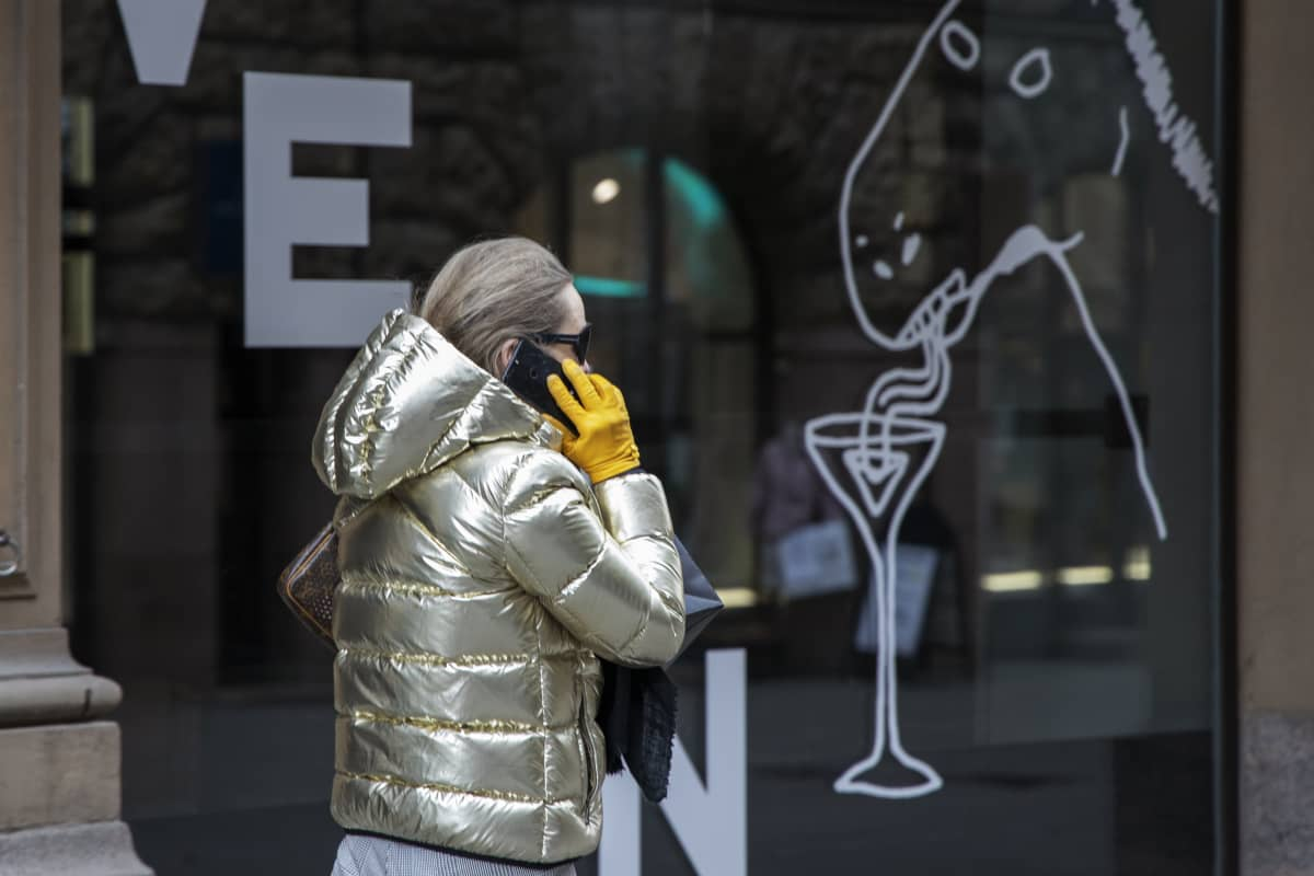 Nainen puhuu kadulla puhelimeen.