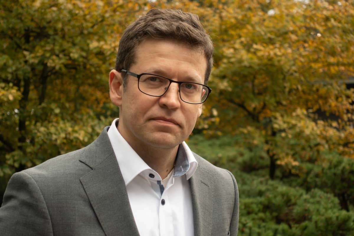 Fortumin johtaja Simon-Erik Ollus, pääkonttorin edessä Espoon Keilaniemessä. Asusteina valkonen kauluspaita, harmaa puvun takki ja silmälasit. On syksyinen pilvinen päivä ja taustalla puiden lehdet ovat keltaisia.