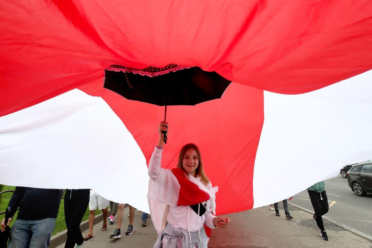 Nainen kannatteli sateenvarjolla suurta punavalkoista kangasta Minskissä Valko-Venäjällä ennen suurmielenosoituksen alkua 6. syyskuuta 2020. Punavalkoinen lippu on noussut opposition symboliksi mielenosoituksissa.