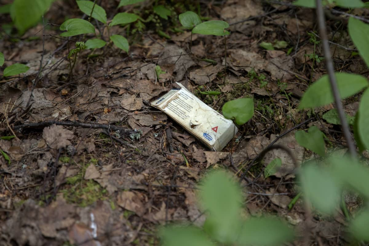 Kolmiolääkepaketti maassa metsässä.