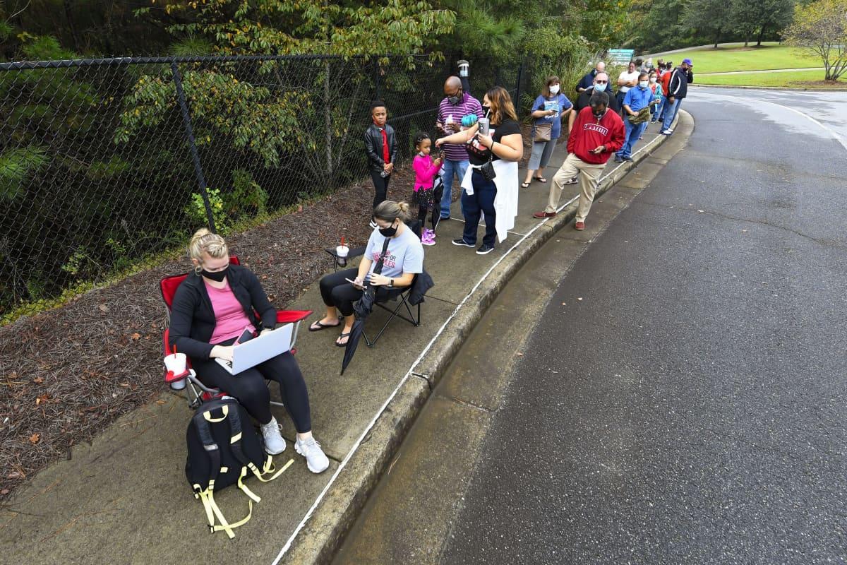 Ihmisiä jonottaa ennakkoäänestämään Georgiassa. Etualalla jonossa oleva nainen istuu tuolissa ja katsoo sylissään olevaa tietokonetta.