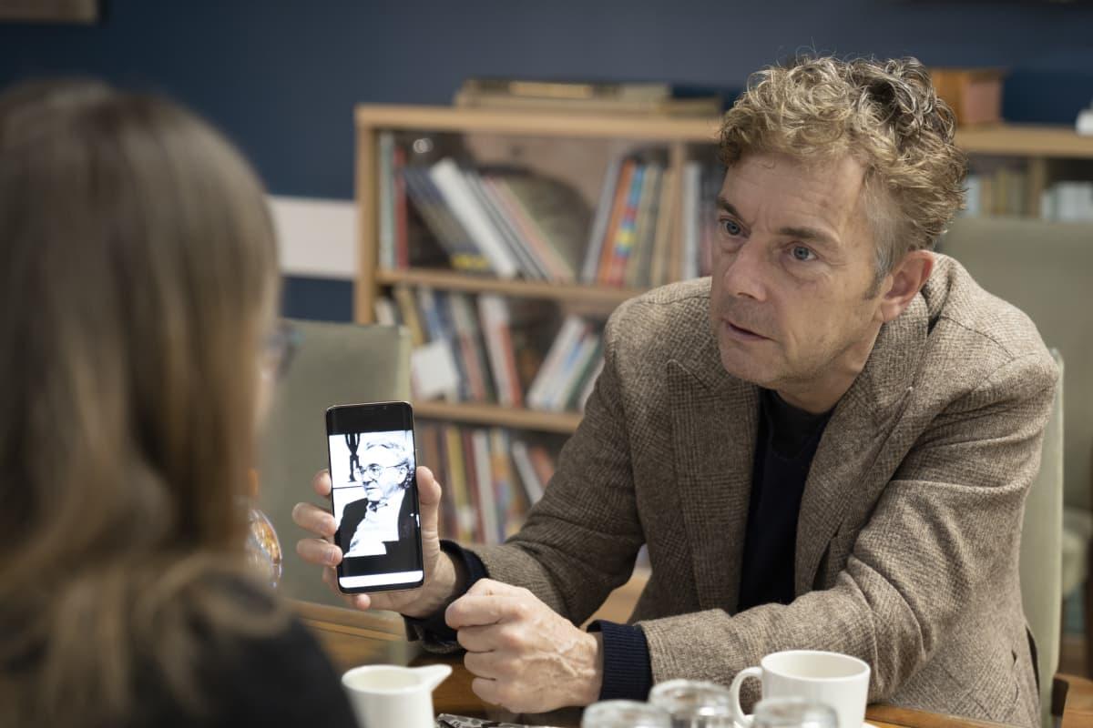 Melcher de Wind , kirjailijan poika ,pitelee kännykkää jossa isän kuva