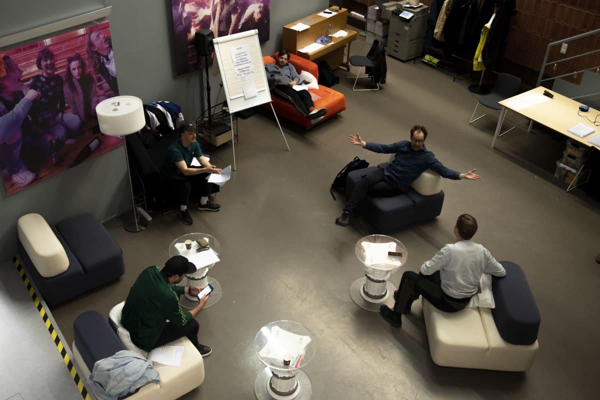 Kuvassa Dingo-kuunnelman näyttelijöitä harjoittelemassa taukotilassa, kuvattuna yläviistosta.