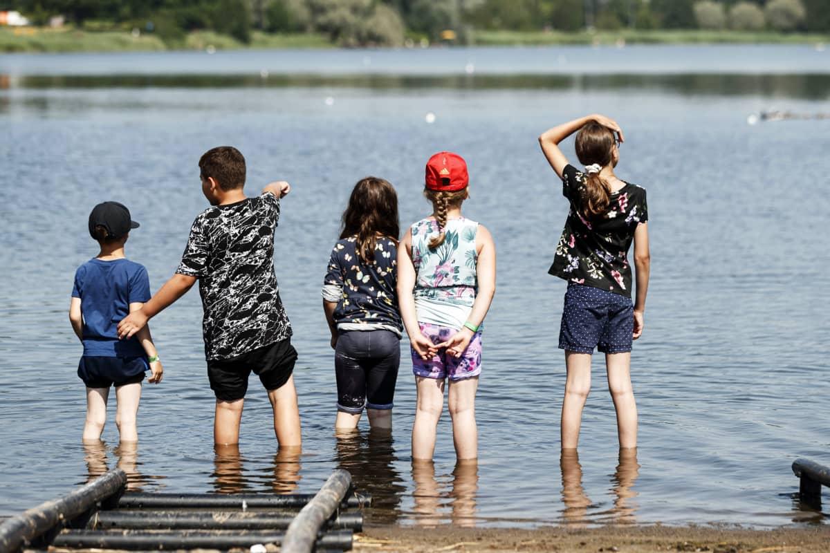 Ihmiset seisovat rivissä vedessä.