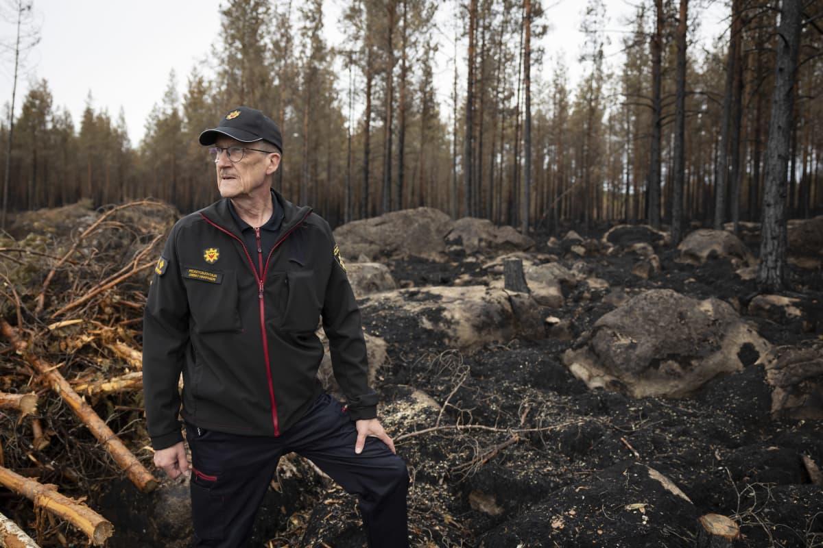 Pelastusjohtaja Jarmo Haapanen taustallaan palanutta metsää.