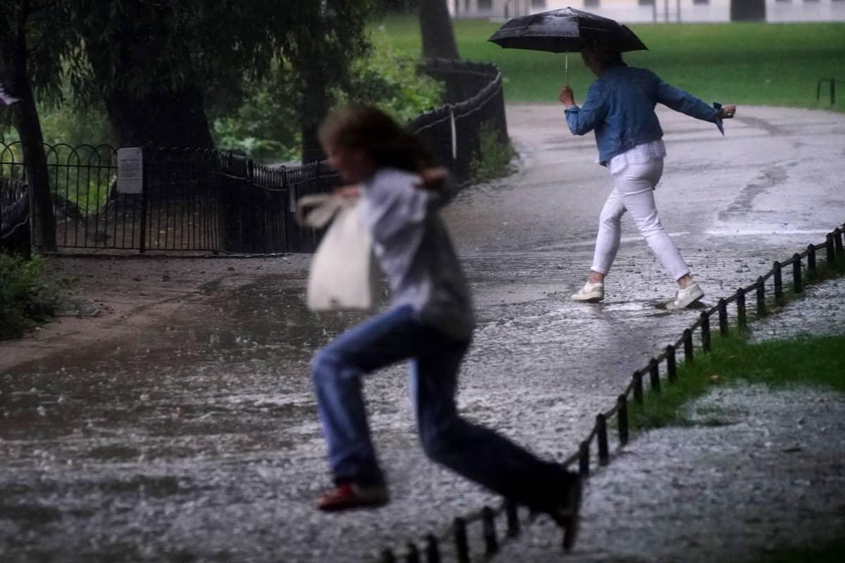 Ihmiset loikkivat tulvivalla tiellä.